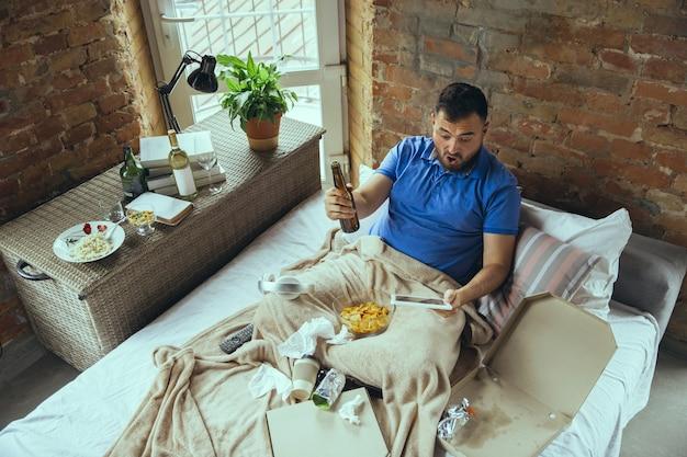 Luie man die in zijn bed woont, omringd door rommelig. je hoeft niet de deur uit om gelukkig te zijn