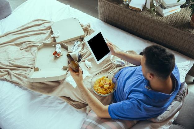 Luie man leeft het hele leven in zijn bed, omringd door rommel