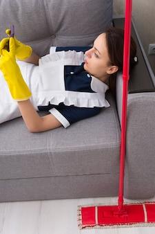 Luie meid of huishoudster die een pauze neemt en ontspant op een bank met haar dweil naast haar die een sms-bericht leest op haar mobiele telefoon, van bovenaf bekijken