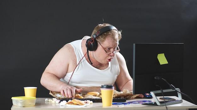 Luie, mollige man in een t-shirt en een koptelefoon zwerft over het web. mensen houden van computerspellen. het concept van verslaving