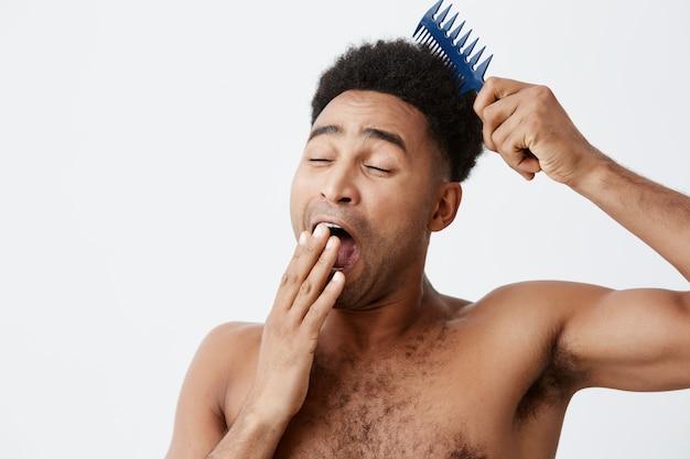 Luie ochtend. portret van grappig knap afro amerikaans mannetje met krullend haar zonder kleren die mond kleden, geeuw die haar in ochtend proberen te kammen.