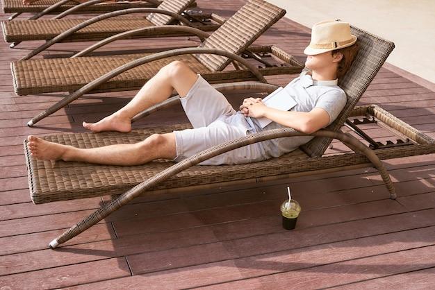 Luie tijd. aziatische man slaapt in de zomer op het bankzwembad