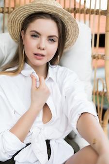 Luie tijd in comfortabele stoel. mooie jonge vrouw ontspannen in een grote comfortabele stoel op het terras van haar buitenhuis