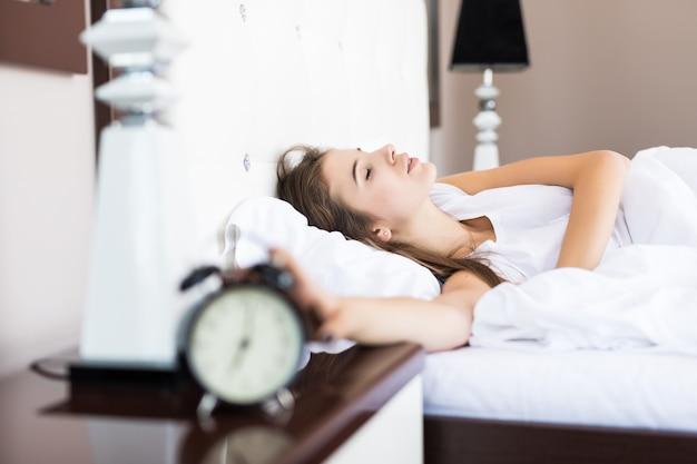 Luie vrouw blijft liggen nadat de wekker 's ochtends afging