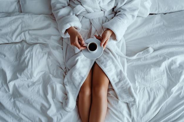 Luie vrouw die badjas draagt die op bed ligt en geniet van aromatische koffiekop tijdens het ontspannen in gezellige comfort slaapkamer in hotelkamer.