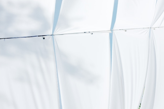 Luifel over blauwe hemel. lucht en wolken bekijken van onderaf tussen witte canvas dak