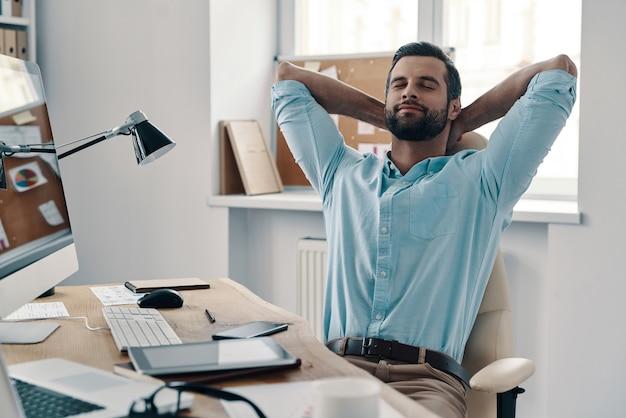 Luiheid. jonge moderne zakenman die zijn handen achter het hoofd houdt en glimlacht terwijl hij op kantoor zit