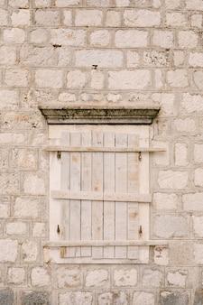 Luiken aan de muur van een oud bakstenen huis