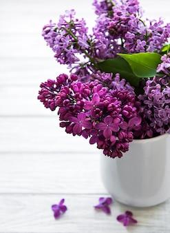 Luilac bloemen in een vaas op een witte houten tafel