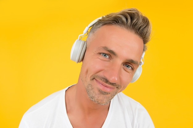 Luister je goed. man van middelbare leeftijd draagt koptelefoon gele achtergrond. engelse school. vreemde taal leren. audio cursussen. luisteroefening. modern onderwijs. luister technologie.