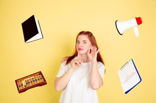 Luister naar iemand. het portret van de kaukasische jonge vrouw op gele studioachtergrond, teveel taken. hoe u de juiste tijd kunt beheren. concept van werken, zaken, financiën, freelance, zelfmanagement, planning.