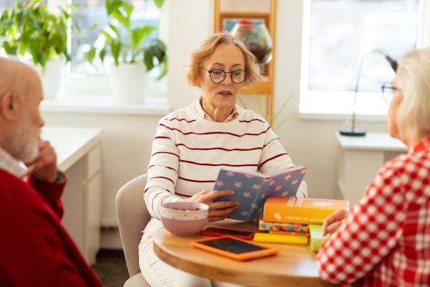 Luister nu. knappe aardige vrouw die in het boek kijkt terwijl ze het aan haar vrienden voorleest