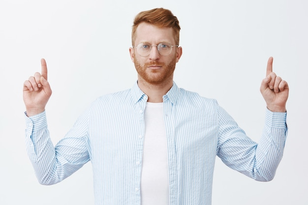 Luister team, eis om ons inkomen twee keer te verhogen. knappe serieuze en slimme zakenman met rood haar in bril en shirt, wijsvingers opheffend om naar boven te wijzen, staande over grijze muur kalm