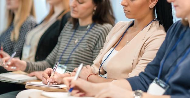 Luisteraars maken aantekeningen in notitieboekjes, zittend in de vergaderruimte