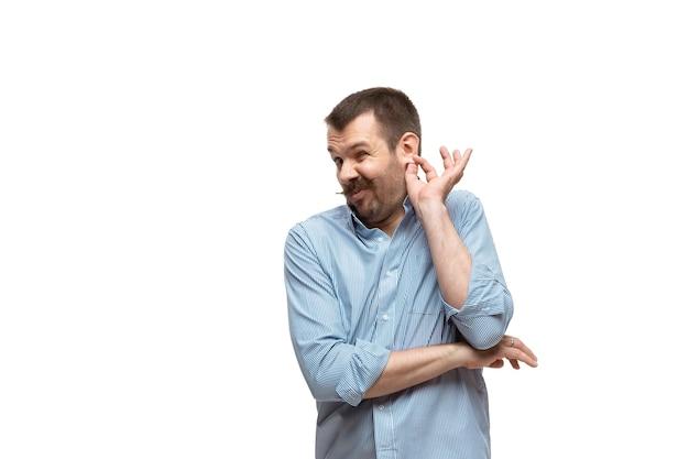 Luisteren. jonge man met grappige, ongebruikelijke populaire emoties en gebaren geïsoleerd op een witte studio achtergrond. menselijke emoties, gezichtsuitdrukking, verkoop, advertentieconcept. trendy look geïnspireerd op memes.