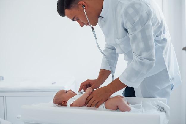 Luisteren met behulp van een stethoscoop. jonge kinderarts is overdag met kleine baby in de kliniek.