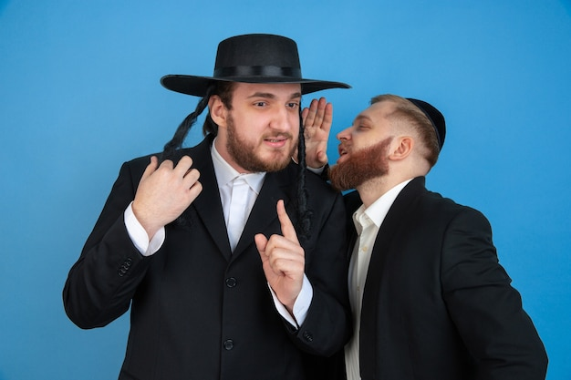Luisteren naar geheimen. portret van een jonge orthodoxe joodse mannen geïsoleerd op blauwe muur. purim, zaken, festival, vakantie, viering pesach of pesach, jodendom, religie concept.