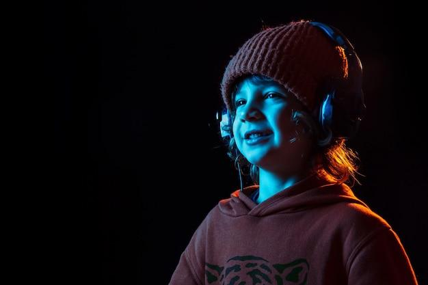 Luisteren naar muziek en dansen. portret van een blanke jongen op een donkere muur in neonlicht. prachtig krullend model. concept van menselijke emoties, gezichtsuitdrukking, verkoop, advertentie, moderne technologie, gadgets.