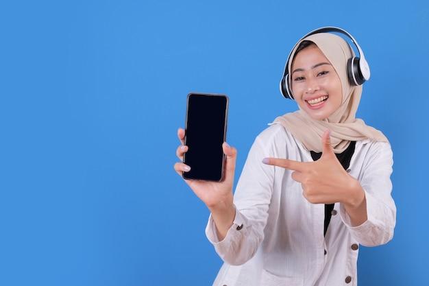 Luisteren naar muziek en pratende telefoon met koptelefoon. jonge vrouwelijke persoon wijzende telefoon