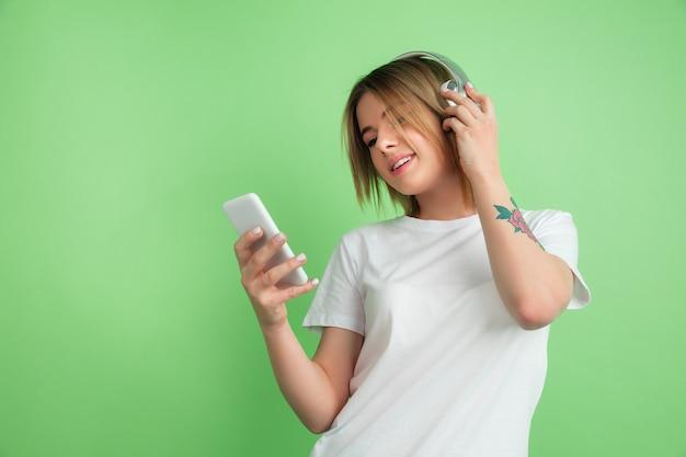 Luisteren naar muziek. portret van de blanke jonge vrouw geïsoleerd op groene studio muur.