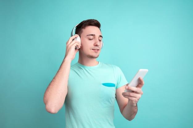 Luisteren naar muziek. portret van een blanke jongeman geïsoleerd op een blauwe studiomuur