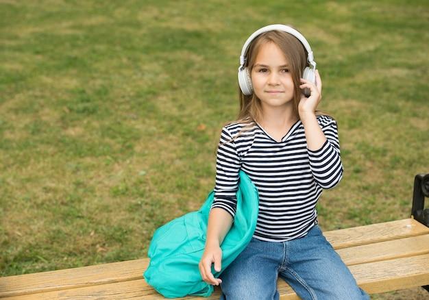 Luisteren naar nieuwe deuntjes. klein kind luistert naar muziek zomer buitenshuis. luistervaardigheid. audio leren. engelse school. cursussen vreemde talen. luistervaardigheid. muzikale opvoeding, kopieer ruimte.