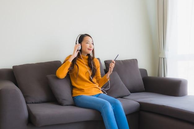 Luistert de portret jonge aziatische vrouw die slimme mobiele telefoon met hoofdtelefoon met behulp van voor muziek op bank