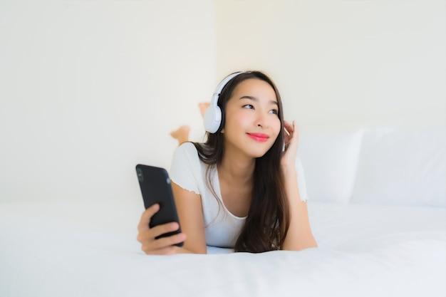Luistert de portret mooie jonge aziatische vrouw gelukkige glimlach met slimme mobiele telefoon en hoofdtelefoon voor muziek