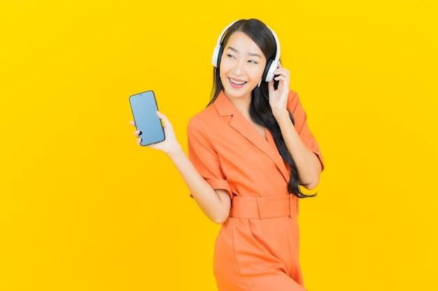 Luistert de portret mooie jonge aziatische vrouw met hoofdtelefoon en slimme mobiele telefoon aan muziek op geel