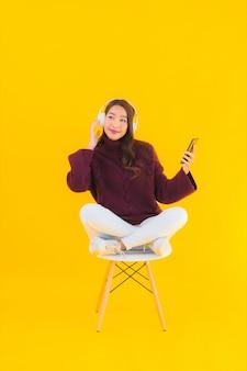 Luistert de slimme mobiele telefoon van de portret mooie jonge aziatische vrouw muziek