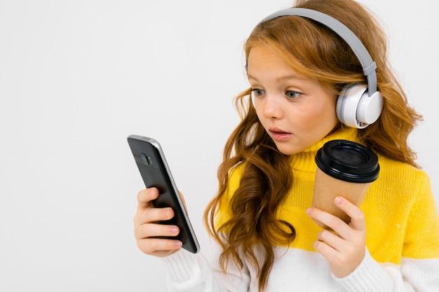 Luistert het tiener kaukasische meisje met gele hoed aan muziek met grote oortelefoons, telefoon en serfing internet dat op wit wordt geïsoleerd