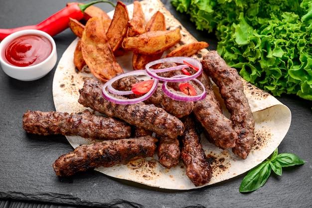 Lula kebab met aardappelen, groenten en saus, op een zwarte ondergrond