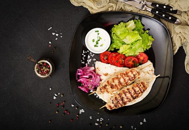 Lula kebab van gegrilde kalkoen (kip) met verse groenten. bovenaanzicht