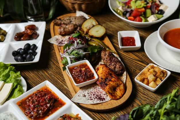 Lula-kebab van vlees en kip geserveerd met mangal salade