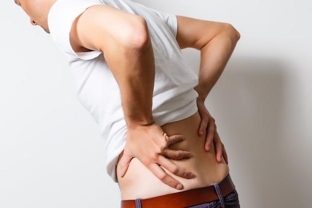 Lumbago symptoom. jonge man met zijn pijnlijke ontstoken lendenen. gezondheidszorg en medicijnen.