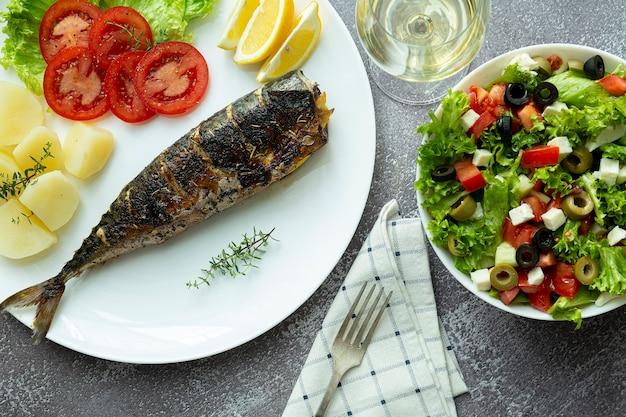 Lunch. gebakken makreel op een witte plaat met aardappelen en frisse salade, witte wijn, bovenaanzicht