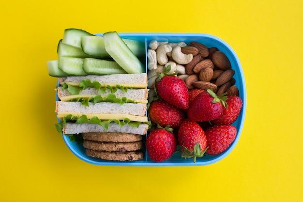 Lunch in de blauwe doos in het midden van het gele oppervlak. bovenaanzicht.