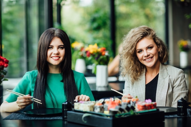 Lunch in een chinees restaurant op het zomerterras. blonde en brunette meisjes eten sushi met chinese stokjes. sushi tijd concept.
