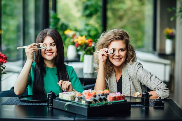 Lunch in een chinees restaurant op het zomerterras. twee zussen eten sushi met chinese stokjes.