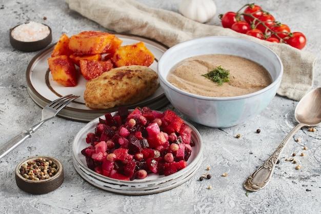 Lunch in kom en borden met vork en lepel, keukendoek en tomaten op lichte marmeren achtergrond