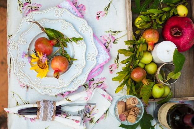 Lunch is romantisch in de herfsttuin, sfeer van vakantie en gezelligheid. herfst diner in de open lucht met wijn en fruit. decortafel met bloemen en granaatappel. oude foto.