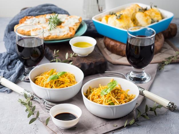 Lunch met currypastanoedels in kommen en groenten met kurkuma