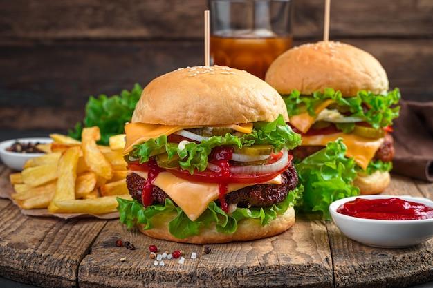 Lunch met hamburgers op een bruine achtergrond. twee sappige burgers met frietjes en cola. fast food.
