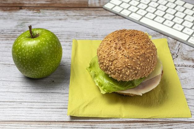 Lunch op de werkplek gezonde sandwich in de buurt van laptop op werktafel. thuisvoedsel voor kantoorconcept
