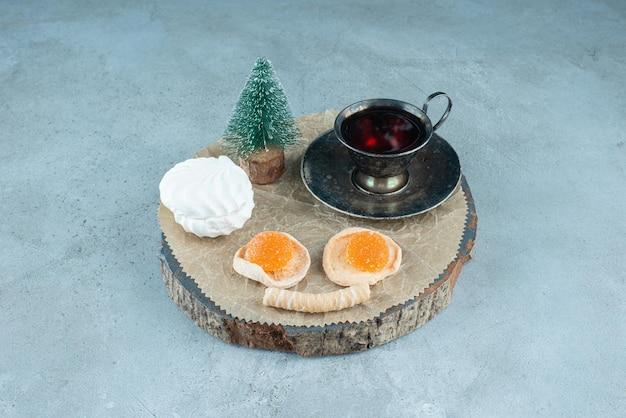 Luncharrangement van thee, bundel desserts en een boomfiguur op een houten plank op marmer.