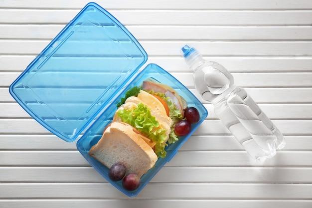 Lunchbox en fles water op houten achtergrond