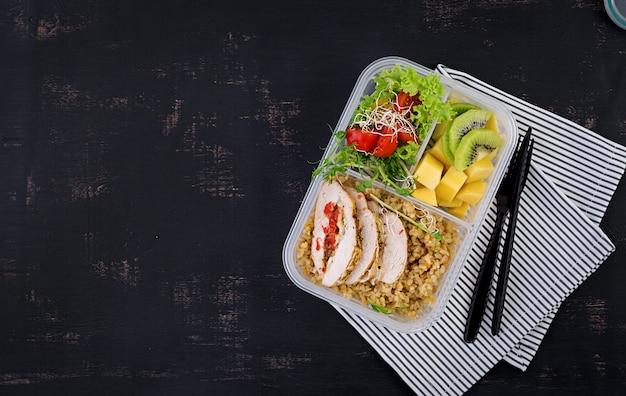 Lunchbox kip, bulgur, microgreens, tomaat en fruit. gezond fitness eten. afhalen. lunchbox. bovenaanzicht