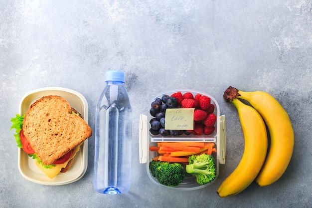 Lunchbox met de fles van de wortelenbroccoli van sandwichbessen waterbanaan op grijs