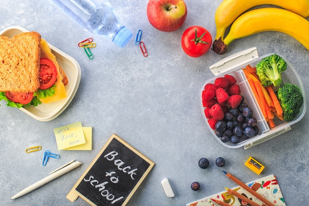 Lunchbox met de fles van de wortelenbroccoli van sandwichbessen waterbanaan op grijze hoogste mening