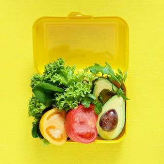 Lunchbox met een snack van sla, tomaat, avacado op een gele muur. gezond eten concept. wordt veganist. lekker vegetarisch eten in plastic doos.
